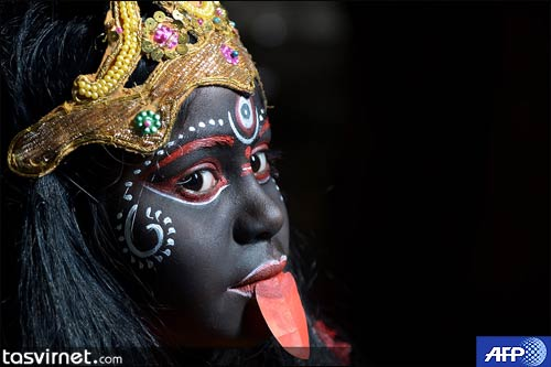 دختر هندی در لباس الهه هندو (کالی) در حال تمرین قبل از شرکت در یک جشن دینی Gajan در کلکته